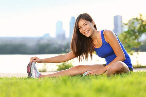 Exercise xwoman stretching hamstring leg muscles duing outdoor running workout. Smiling happy mixed race Asian Chinese / Caucasian sport fitness model in city park. Click for more: