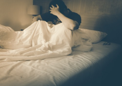 Blurry young man, unable sleep because of stress problems. Vintage warm tone.