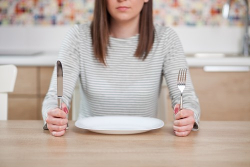 Displeased young woman sitting at the empty plate. Shallow depth of field, focus on foreground